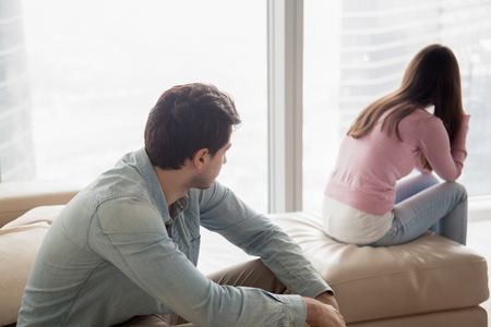 Young couple sitting apart indoors after quarrel. Offended girl ignoring boyfriend, looking away, serious man thinking about problem in relationships, family conflict, misunderstanding between teens