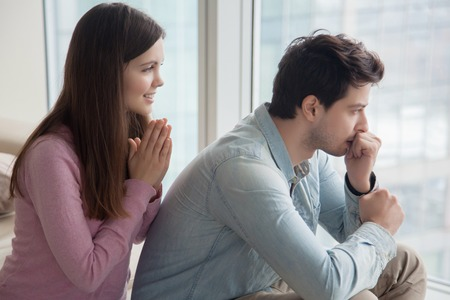Young woman apologizing upset frustrated man at home. Girlfriend asking boyfriend for forgiveness. Girl trying to convince guy to forgive her telling she regrets. Excuses, saying I m sorry, please