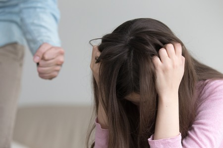 Young woman suffering from domestic violence and cruel abuse of women, furious guy intending to hit his girlfriend, showing fist, beating a girl, wife troubled with family tyranny and despotism