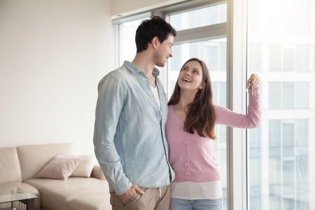householder: Young smiling couple holding and showing keys of their new own home, happy family buying or renting house or apartment, paid real estate mortgage, teenagers left parental home, starting married life Stock Photo