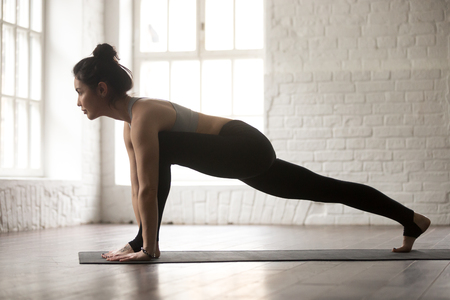 ashtanga: Young attractive woman practicing yoga, stretching in Utthan Pristhasana exercise, Lizard pose, working out wearing black sportswear bra and pants, full length, white loft studio background, side view