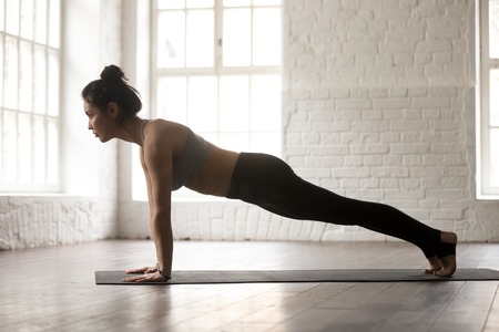 Young attractive woman practicing yoga, standing in Push ups or press ups exercise, Plank pose, working out, wearing sportswear bra and pants, full length, white loft studio background, side view Reklamní fotografie