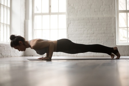 Joven mujer atractiva practicar yoga, de pie en chaturanga dandasana ejercicio, cuatro limbed personal, Push ups o presionar ups plantean, trabajando, blanco loft estudio de fondo, de longitud completa, vista lateral Foto de archivo