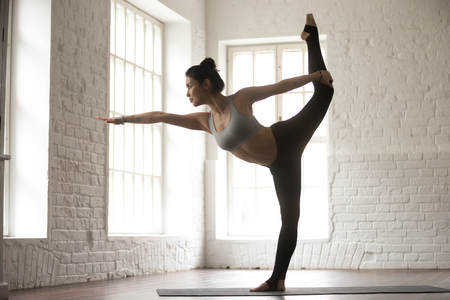 asana: Young attractive woman practicing yoga, standing in Natarajasana exercise, Lord of the Dance pose, working out, wearing sportswear bra and pants, white loft studio background, full length, side view Stock Photo