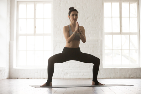 Portrait of young attractive yogi woman practicing yoga concept, standing in Sumo Squat exercise, Goddess pose, working out, wearing sportswear bra and pants, full length, white loft studio background Stock Photo