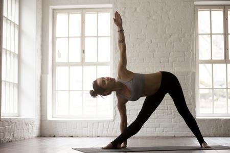 Concepto practicante de la yoga de la mujer atractiva joven de la yogui, colocándose en el ejercicio de Utthita Trikonasana, actitud extendida del triángulo, resolviéndose, vistiendo la ropa de deportes, fondo integral, blanco del estudio, horizontal