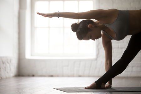 Side view portrait of young yogi woman practicing yoga concept, standing in Utthita Trikonasana exercise, extended triangle pose, working out, wearing sportswear, white loft studio background, closeup
