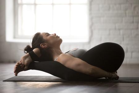 Young attractive yogi woman practicing yoga concept, lying in deep forward bend Yoga Nidrasana exercise, Yogic Sleep pose, working out wearing black sportswear, full length, white studio background