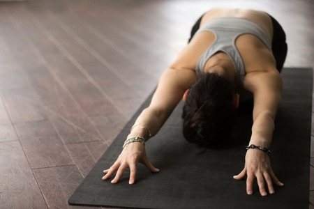 ardha: Young beautiful sporty yogi woman practicing yoga concept, sitting in Child exercise, Balasana pose, working out, wearing sportswear, wrist bracelet, studio background, wooden floor, copy space