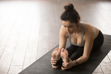 situp: Yogi woman practicing yoga concept, sitting in paschimottanasana exercise, Seated forward bend pose, working out, wearing black sportswear, wooden floor studio background, view from above, copy space Stock Photo