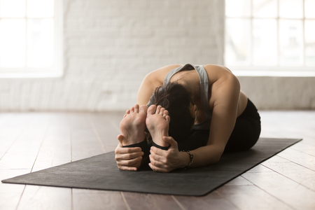 Young attractive yogi woman practicing yoga concept, sitting in paschimottanasana exercise, Seated forward bend pose, working out on black mat, wearing sportswear, white loft studio background