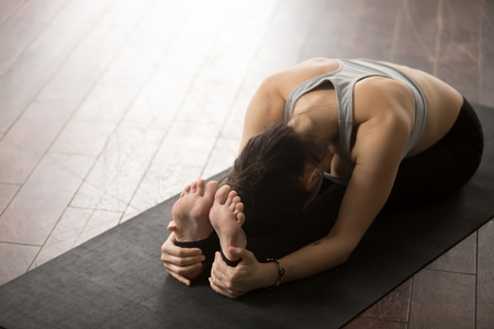 Young sporty yogi woman practicing yoga concept, sitting in paschimottanasana exercise, Seated forward bend pose, working out on black mat, studio wooden floor background. Copy space, high angle view