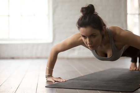 Young attractive fitness woman practicing, doing Push ups or press ups exercise, working out on black mat wearing sportswear, close up portrait, loft background. Weight loss, healthy lifestyle concept