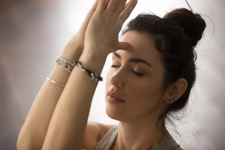 ashtanga: Young attractive yogi woman practicing yoga concept, doing namaste gesture, namaste hands to forehead with her eyes closed, working out, wearing wrist bracelets, studio background, closeup portrait