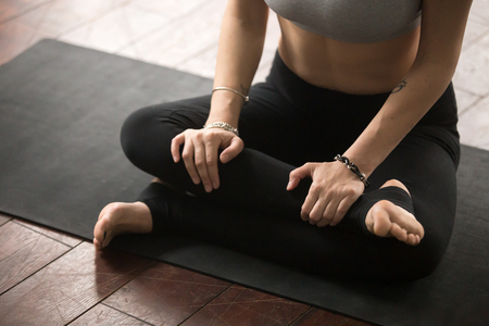 Young yogi woman practicing yoga concept, sitting on the floor in Agni stambhasana exercise, Fire Log, Ankle to Knee pose, working out, wearing sportswear bra and pants, close up midsection. Indoor