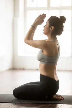 Young attractive yogi woman practicing yoga concept, sitting in vajrasana exercise, seiza pose with namaste, working out wearing sportswear, full length, loft studio background, vertical side view