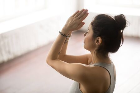 Young beautiful yogi woman practicing yoga concept, doing namaste gesture with her eyes closed, working out, wearing wrist bracelets, loft studio background, close up