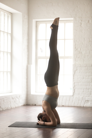 headstand: Young attractive yogi woman practicing yoga concept, standing in salamba sirsasana exercise, headstand pose, working out, wearing sportswear, full length, white loft studio background, vertical