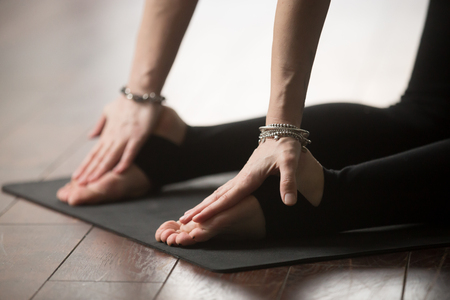 Young yogi woman practicing yoga concept, stretching in Ustrasana exercise, Camel pose, working out on black mat on studio floor, wearing wrist bracelet accessories, close up of hands Reklamní fotografie - 75256105