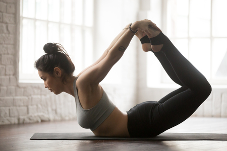dhanurasana: Young attractive cool yogi woman practicing yoga concept, stretching in Dhanurasana exercise, Bow pose, working out wearing black sportswear, full length silhouette on white loft studio background