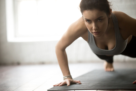 Young sporty cool woman practicing yoga, doing Push ups or press ups exercise, working out on black mat wearing sportswear, close up portrait, loft background. Weight loss, healthy lifestyle concept