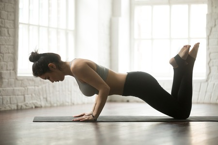 Young attractive woman doing Warming up, practicing Exercises for chest, arms, and shoulders, knee Push ups or press ups, working out, wearing sportswear, full length, white loft studio background