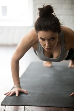 Young resolute woman practicing yoga, doing Push ups or press ups exercise, working out on black mat, close up portrait, loft background. Weight loss, healthy lifestyle concept, vertical photo