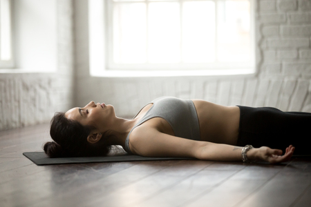 Young attractive yogi woman practicing yoga concept, lying in Dead Body, Savasana exercise, Corpse pose, working out, wearing sportswear, close up portrait, white loft studio background Stock Photo