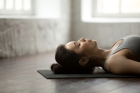Young cool attractive yogi woman practicing yoga concept, lying in Dead Body, Corpse exercise, Savasana pose, working out, wearing sportswear, closeup, white loft studio or home background