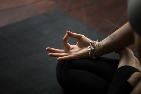Close up of young woman hand with tattoo and wrist bracelets practicing yoga, sitting in Padmasana exercise on black mat, Lotus pose with mudra gesture, working out, meditating, copy space background