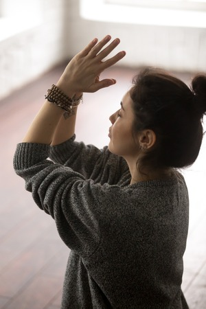 Young attractive yogi woman practicing yoga concept, making namaste gesture, working out, wearing grey oversized sweater, closeup, white loft studio background, vertical photo
