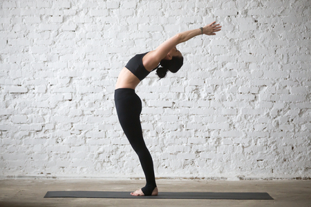 Young yogi attractive woman practicing yoga concept, stretching in Ardha Chakrasana exercise, Standing Backward Bend pose, working out, wearing black sportswear, full length, white loft background Stockfoto