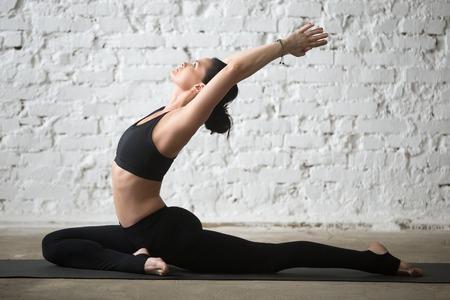 Young yogi woman practicing yoga concept, stretching in Single Pigeon exercise, Eka Pada Raja Kapotasana, One Legged King Pigeon pose, working out in sportswear, full length, white loft background