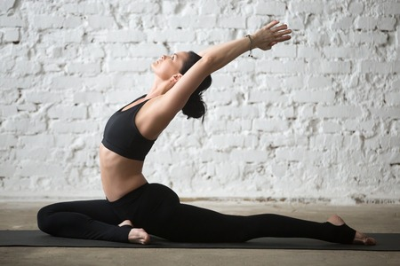 Young yogi woman practicing yoga concept, stretching in Single Pigeon exercise, Eka Pada Raja Kapotasana, One Legged King Pigeon pose, working out in sportswear, full length, white loft background