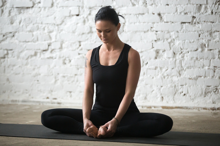 Young yogi attractive woman practicing yoga concept, sitting in Butterfly exercise, baddha konasana pose, working out, wearing sportswear, black tank top and pants, full length, white loft background Stok Fotoğraf - 75818227