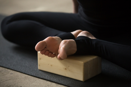 Yogi sporty woman practicing yoga concept, sitting in Butterfly exercise, advanced baddha konasana pose, using wooden block, working out, wearing sportswear pants, white loft background, legs close up Stock Photo