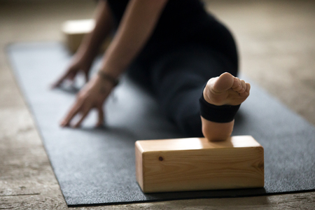 Young yogi woman practicing yoga concept, doing advanced splits, Straight Angle exercise, Samakonasana pose using blocks for deep stretch, working out on mat wearing black pants, leg close up, studio