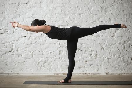 운동 요가 개념을 연습하는 젊은 요기 매력적인 여자 세 운동, Virabhadrasana III 포즈, 운동, 검은 바지, 전체 길이, 흰색 로프트 배경 입고 운동