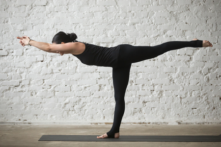 Jonge yogi aantrekkelijke vrouw beoefenen van yoga-concept, staande in Warrior drie oefening, Virabhadrasana III pose, uit te werken, het dragen van sportkleding, zwarte broek, volledige lengte, witte loft achtergrond