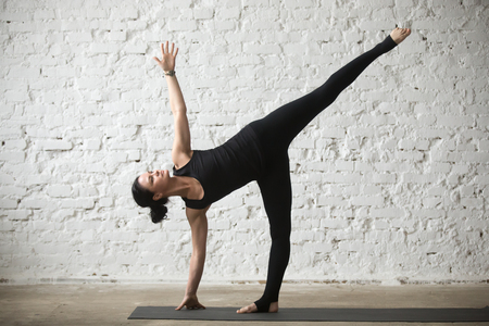 Young yogi attractive woman practicing yoga concept, standing in Half Moon exercise, Ardha Chandrasana pose, working out, wearing sportswear, black tank top and pants, full length, white background Stock Photo