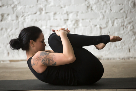 Young yogi attractive woman practicing yoga concept, stretching in Knees to Chest exercise, Apanasana pose, working out, wearing sportswear, black tank top and pants, full length, loft background Banco de Imagens