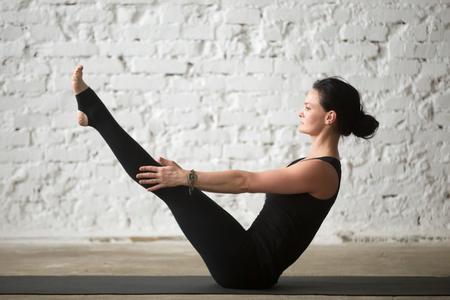 Jeune yogi femme attrayante pratiquant le concept de yoga, étirement à Paripurna Navasana exercice, pose d'équilibre, travailleur, vêtement de sport, débardeur noir et pantalons, pleine longueur, loft fond