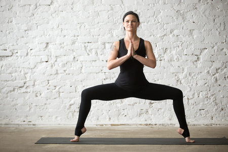 Middle aged yogi attractive woman practicing yoga concept, doing Sumo Squat exercise, Goddess pose, working out, wearing sportswear, black tank top and pants, full length, white loft background