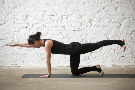 Young yogi attractive woman practicing yoga concept, standing in Donkey, Kick exercise, Bird dog pose, working out, wearing sportswear, black tank top and pants, full length, white loft background Stock Photo