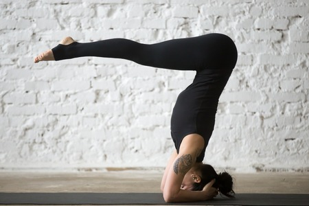 Young yogi attractive woman practicing yoga concept, standing in headstand exercise, variation of salamba sirsasana pose, working out, wearing black sportswear, full length, white loft background Stock Photo