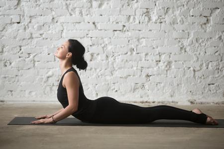 Jonge yogi aantrekkelijke vrouw beoefenen van yoga-concept, die zich uitstrekt in Cobra oefening, Bhujangasana pose, uit te werken, het dragen van sportkleding, zwarte tank top en broek, volledige lengte, witte loft achtergrond