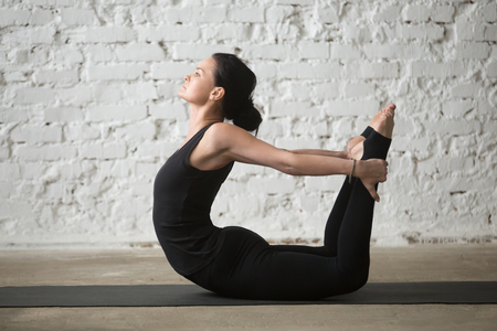 dhanurasana: Young yogi attractive woman practicing yoga concept, stretching in Dhanurasana exercise, Bow pose, working out, wearing sportswear, black tank top and pants, full length, white loft background Stock Photo