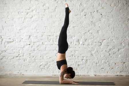 Middle aged yogi woman practicing yoga concept, standing in Pincha Mayurasana exercise, handstand pose, working out, wearing sportswear, black tank top, pants, full length, white loft background Stock Photo