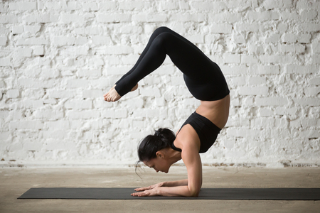 Mid aged yogi attractive woman practicing yoga concept, standing in vrischikasana exercise, Scorpion pose, working out, wearing sportswear, black tank top and pants, full length, white loft background Stock Photo