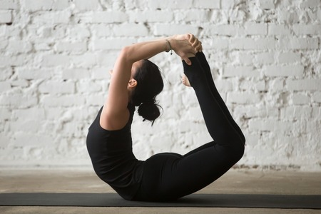 Young yogi attractive woman practicing yoga concept, stretching in Dhanurasana exercise, Bow pose, working out, wearing sportswear, black tank top and pants, full length, white loft background Stock Photo